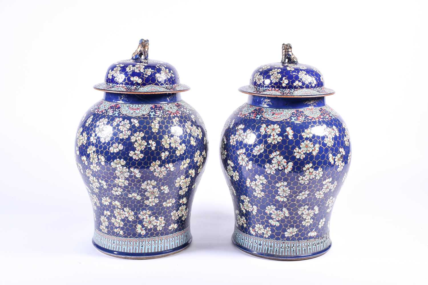 A pair of large Chinese porcelain vases and covers, Qing, 18th century Canton South East Asian Fo dog finials blossoming prunus ruyi heads Famille Rose gilt cracked ice and powder blue ground