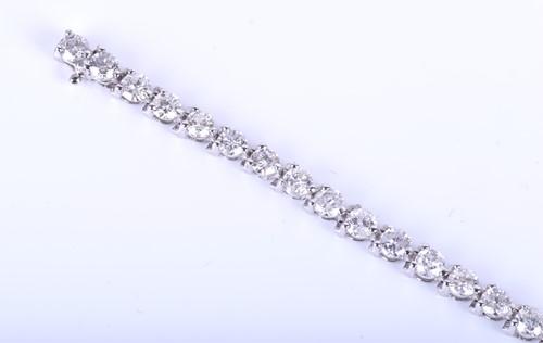 Lot 396 - A 14k white gold and diamond line bracelet,...