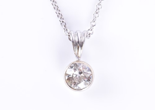 Lot 52-An 18ct white gold and solitaire diamond pendant...