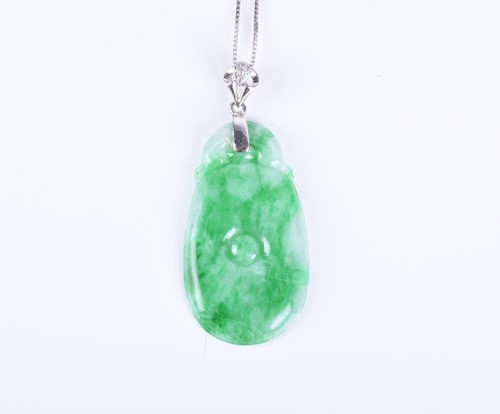Lot 75-A jade and diamond pendant the tapered oval...