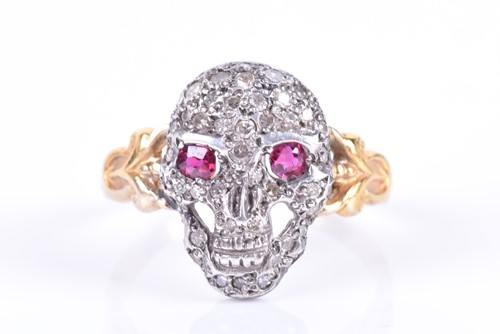 Lot 18A-A yellow metal, silver, and diamond 'skull' ring...
