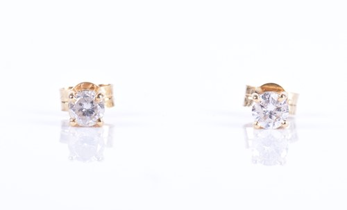 Lot 144-A pair of solitaire diamond ear studs the...