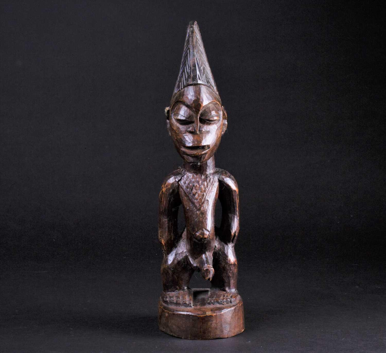 Lot 22 - A Yoruba Ibeji standing male figure, his chest...