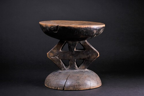 Lot 61 - An African carved wood stool, with a slightly...