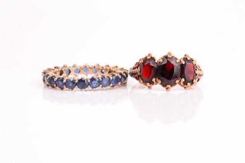 Lot 25 - A three stone half hoop garnet ring, the...