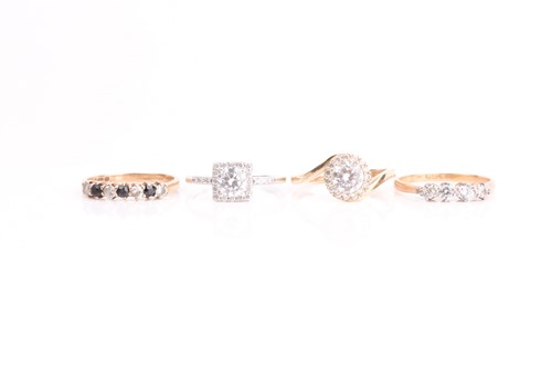 Lot 12 - A four stone half hoop ring, comprising two...