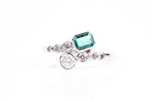 Lot 16 - An emerald and diamond crossover ring, with...