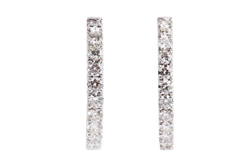 Lot 54 - A fine pair of diamond earrings, each set with...
