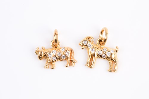 Lot 21 - Two diamond set Zodiac charms, the cast Taurus...