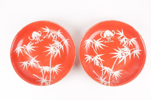 Lot 138 - A pair of coral ground reverse painted bamboo...