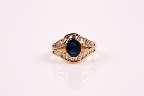 Lot 44 - A sapphire and diamond ring; the oval cut...