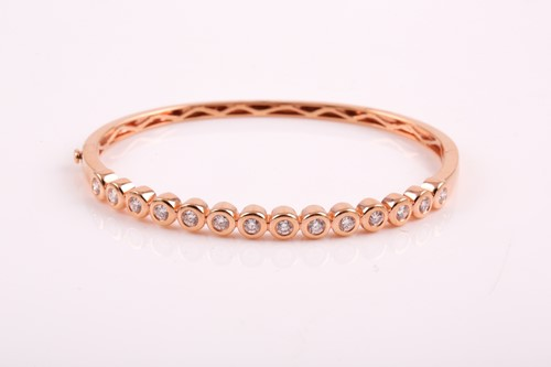 Lot 42 - An 18ct rose gold and diamond bangle, the...