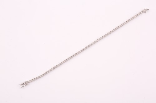 Lot 25 - An 18ct white gold and diamond line bracelet,...