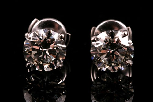 Lot 180 - A pair of round brilliant-cut diamond earrings,...