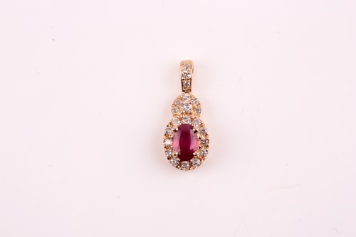 Lot 23 - A 14k yellow gold, diamond, and ruby pendant,...