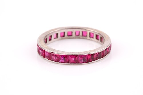 Lot 45 - A white metal and ruby eternity ring,...