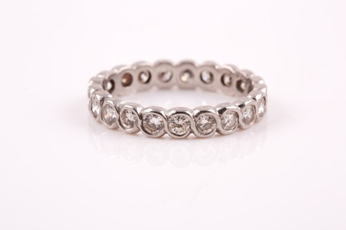 Lot 41 - A diamond eternity ring, rubover set with...