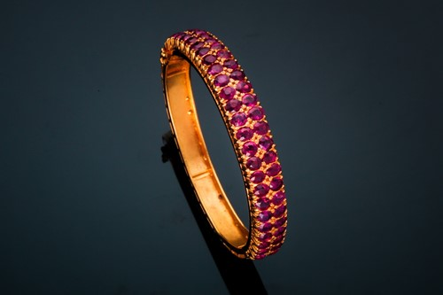 Lot 20 - A ruby bangle; composed of two rows of mixed...