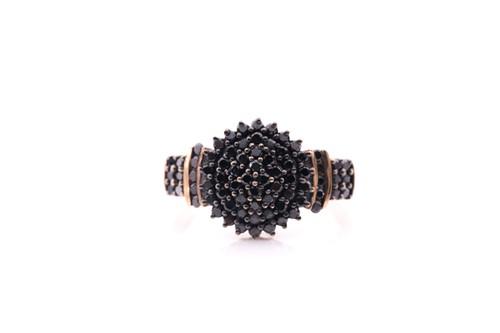 Lot 42 - A black diamond cluster ring; the bombé style...