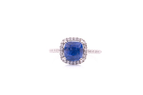 Lot 62 - A sapphire and diamond cluster ring; the...