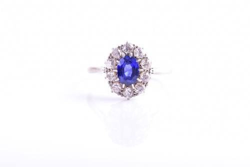 Lot 30 - A diamond and sapphire cluster ring, set with...