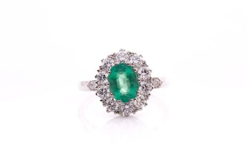 Lot 21 - A platinum, diamond, and emerald cluster ring,...