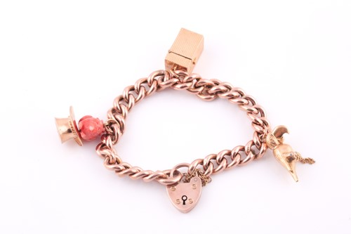 Lot 18 - A 9ct rose gold curb-lik charm bracelet, with...